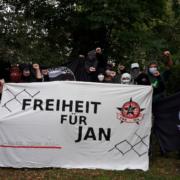 Foto mit vermummten Personen die ein Banner mit der Aufschrift Freiheit für Jan halten sowie eine Antifa Fahne und eine FdA Fahne